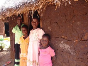 Dorine (left, back) and her school-age siblings standing outside their sleeping hut.