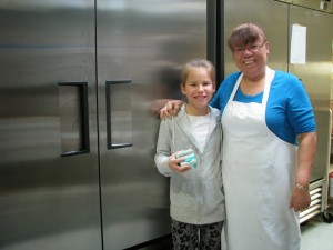 Elsipogtog First Nation School Cook Jean Anne Clement with student Erica standing in front of the brand new milk fridge.