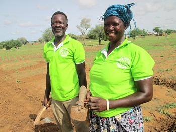 Mr. Akolgo, left, with close cropped hair and grey beard, stands next to Madam Adukpoka on the right. They both wear lime green shirts and are standing in a recently tilled field, holding farm tools.