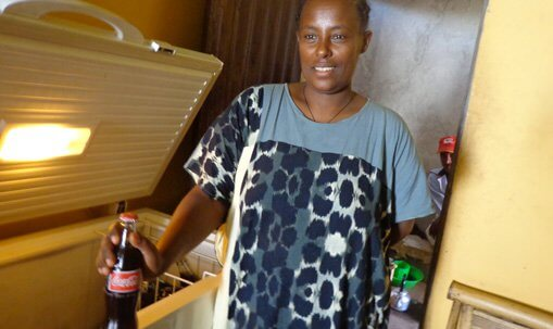 Woinshet Tefera, goat farmer from Ethiopia, stands in front of her new freezer holding a coke