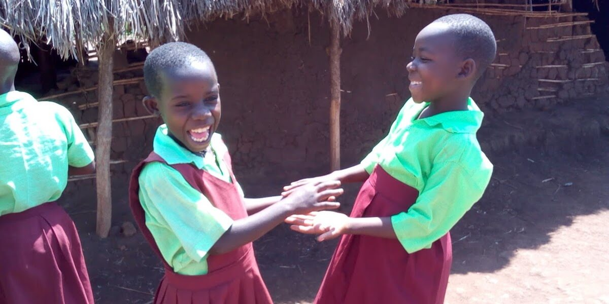 Two girls dressed in their school uniform laughing and playing