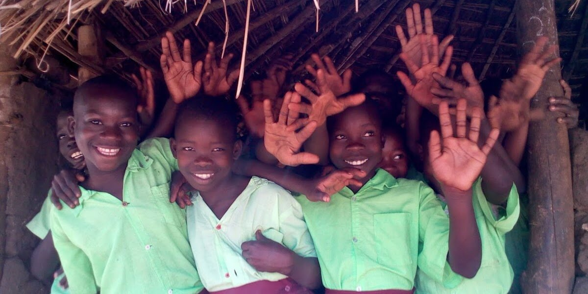 Happy children wave at the camera under the roof of the old school structure.
