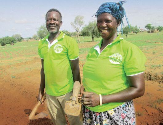 Akolgo and Adukpoka stand in front of the demonstration farm smiling with basic farming tools in their hands.