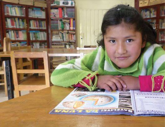 Eight-year-old Araceli sits at a desk reading a magazine in a classroom filled with desks, chairs and a bookcase well-stocked with books.