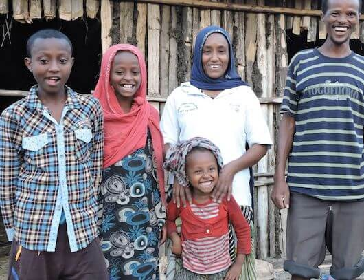 Hawa stands behind her youngest child with two of her children (a boy and a girl) standing off to her right. Her husband stands to her left. They are standing outside their wooden home laughing and smiling.
