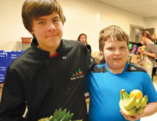 Two boys from the Natoageneg Youth Champions stand close together holding bananas, an orange and a pineapple.