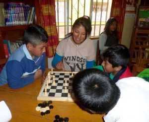 Jhoselin (centre) plays chess with a group of children at Alpacoma Centre