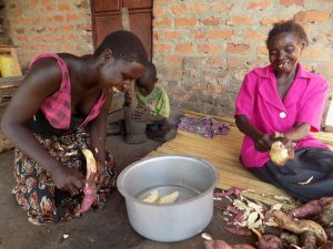 Fall foods: Leonia, right, peels sweet potatoes with her daughter Mary while her grandson prepares ground nuts for lunch.