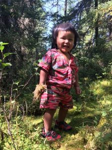 Best.Gift.Ever in Action: A toddler smiles with a handful of plants during a medicine picking trip.