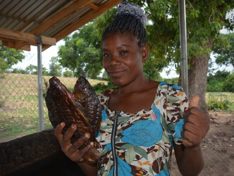 African women Sarah giving a thumbs up while holding two cooked fish
