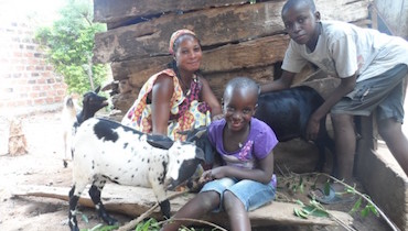 Florence and her two children sit with their goats in their backyard