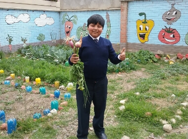 A young boy smiling holding his homegrown crops