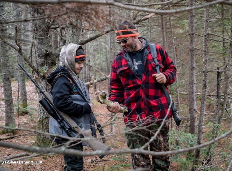 Youth with man in hunting jacket in wooded area. Man holds an animal bone.