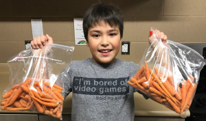 School food ambassador shows off home-grown carrots