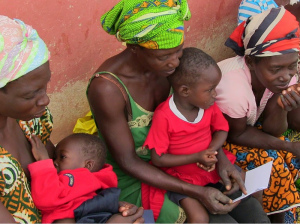 Three women and their children collect their pay-out from a Ghanaian VSLA.