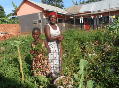 Rebecca and her daughter Praise smiling in their garden with produce