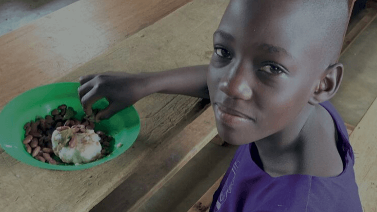 Youth girl eating school meal and looking into camera