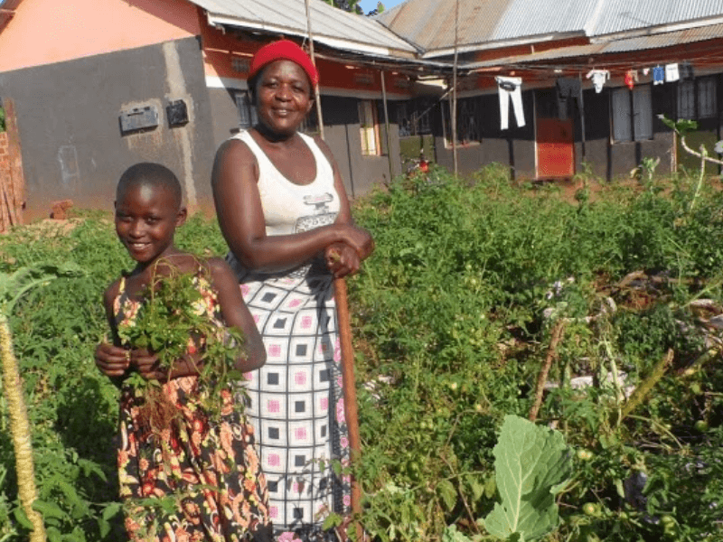 Mother and daugher smile in their garden holding produce