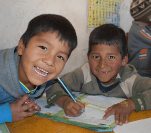 Two boys in Bolivia smiling while doing homework