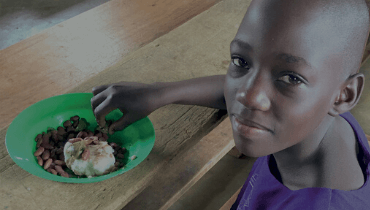 Young girl eating and looking into the camera