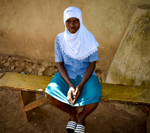 An adolescent girl sits on a bench and looks to the camera