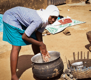 An adolescent girl mixes maize in a pot