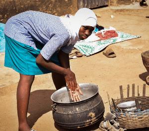 An adolescent girl mixes maize in a pot