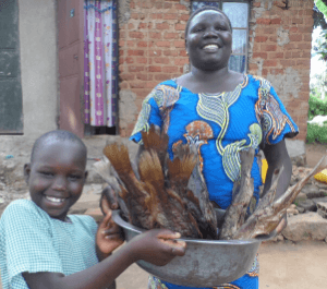 A little girl and her mother smile while holding a basket full of dried fish