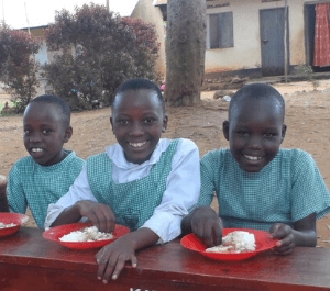Three girls eating lunch on a bench and smiling for the camera