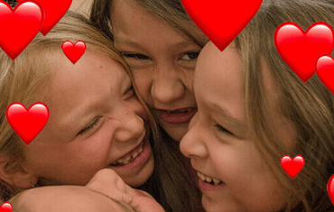 A group of little girls hugging and laughing with cartoon hearts around them