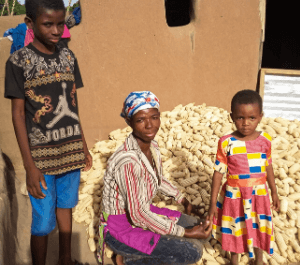 A women stands with her son and daughter and their haul of corn they grew
