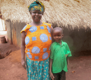 A mother and young son stand in front of their home embracing each other