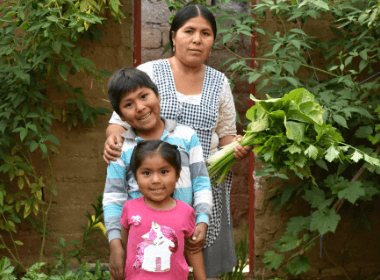A woman stands in her garden with her son and daughter