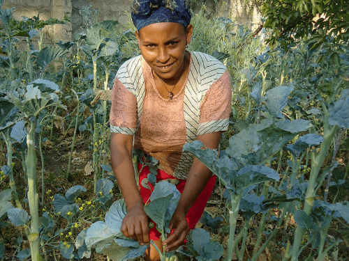 A woman poses holding a plant from her garden