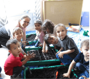 Children planting seeds in classroom garden