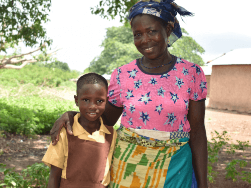 A mother gently puts her arm around her daughter as they smile for the camera
