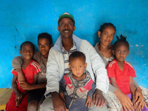 A husband and wife sit with their four children next to them and on their laps, all smiling for the camera