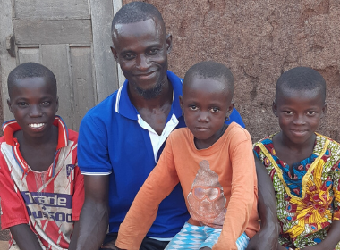 A father sits with his three children in front of his house, one of his children sitting in his lap