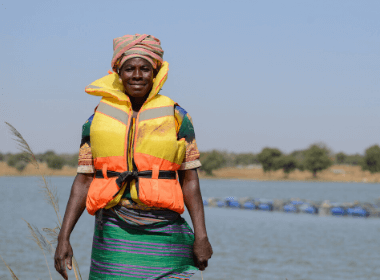 A woman stands in a lifejacket in front of the shoreline, smiling for the camera