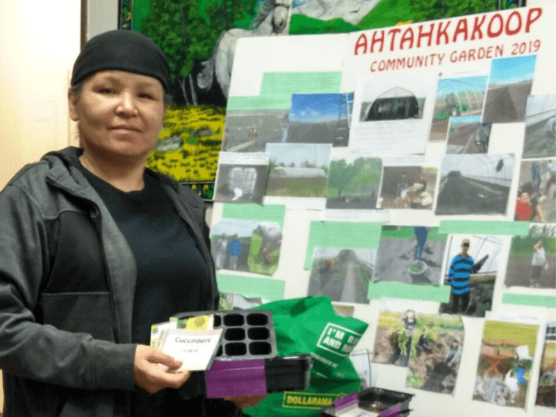 A woman holds a seed packet with a sign that says Ahtahkakoop Community Garden behind her