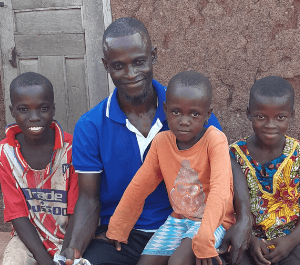 A man sits in front of his house with his three children around him