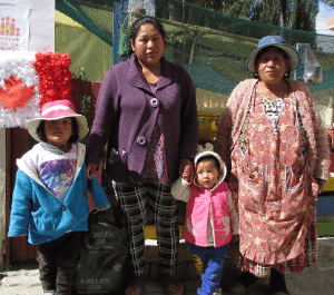 A woman, her mother and her two children stand with an emergency food hamper