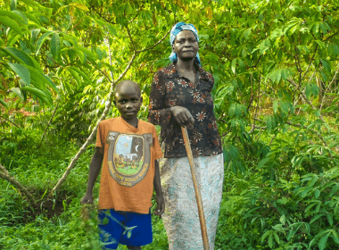 A grandmother and her grandson pose in their family farm