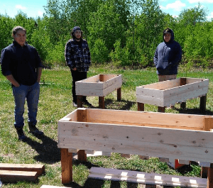 A group of young men pose with wooden flower and vegetable gardens that they've built for the community garden