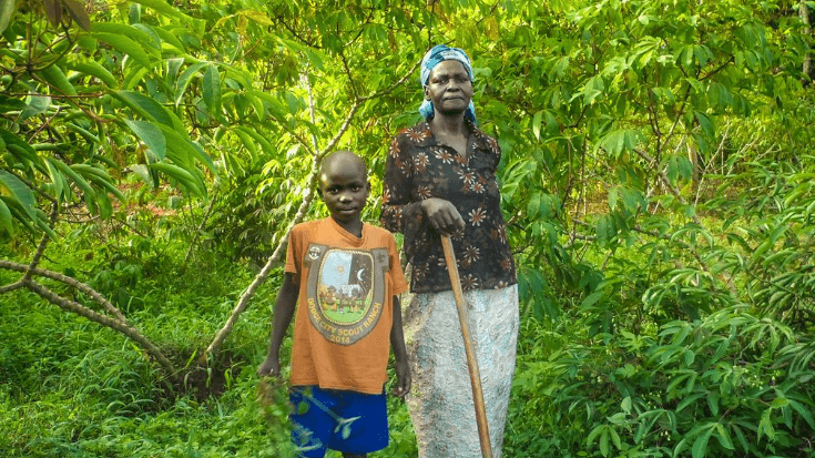A grandmother and her grandson stand in