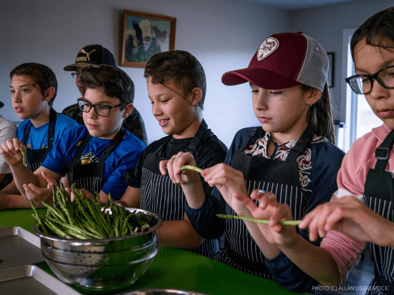 A group of young school kids preparing asparagus in a cooking class