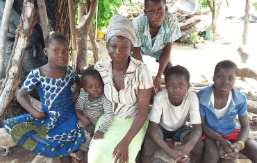 A mother sits with five of her children in front of their house