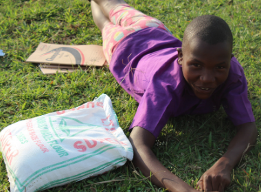 A child lies down in the grass smiling next to a bad of flour