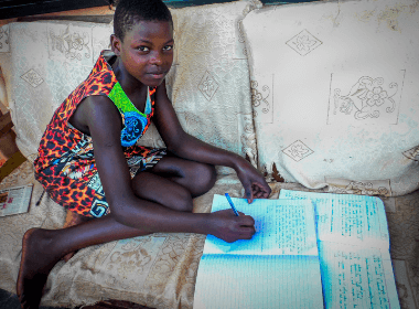 A young girl sits on her couch doing her school work, smiling for the camera