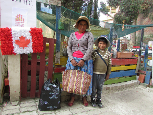 A mother and son stand in front of a fence smiling with food hampers